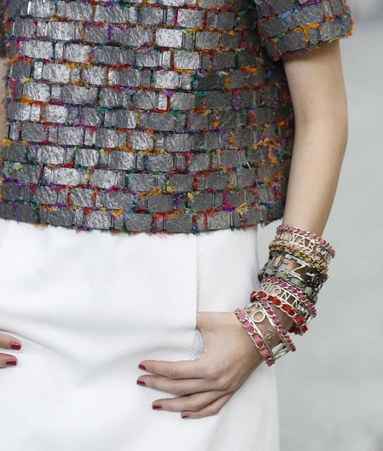 """(CHANEL) - a grife Chanel apostou em braceletes de prata com tiras de couro coloridas com frases como """"make fashion not war"""" (faça moda, não guerras)."""
